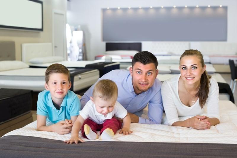 Junge Familie testet Matratze in einem Geschäft