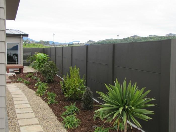 grüne pflanzen vor beton gartenzäune