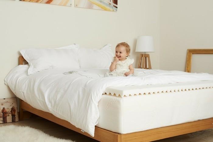 kleines mädchen auf dem bett im schlafzimmer