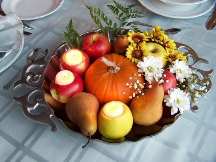 tischdeko für den herbst mit kürbis äpfeln und kerzen