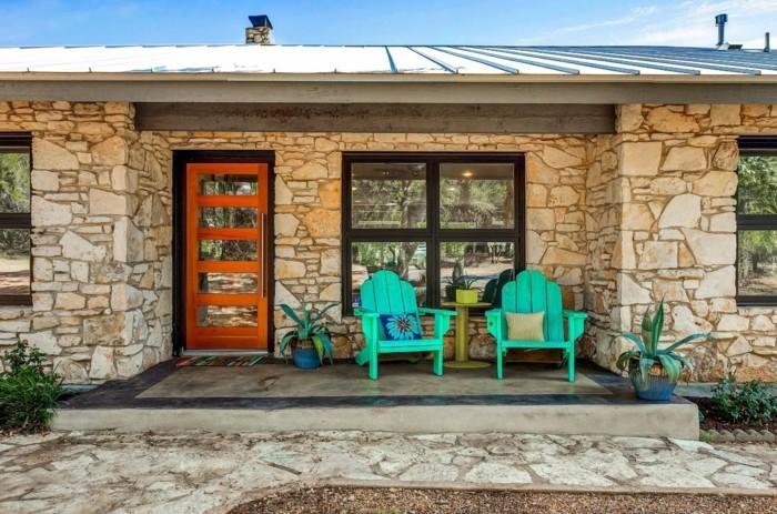 veranda mit grünen holzstühlen und blumentöpfen