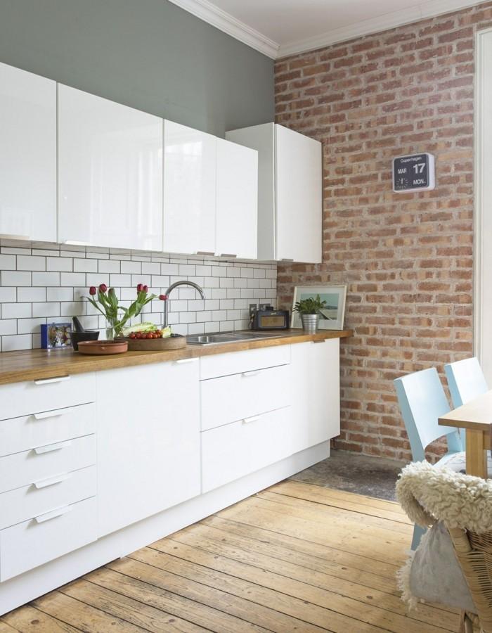 wohnideen küche backsteinwand weiße schranktüren und hölzerner boden
