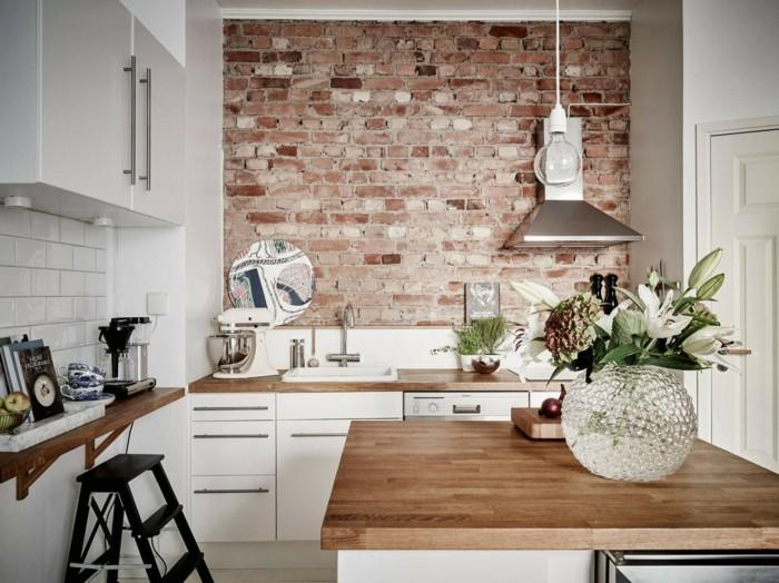 ziegelwand in der küche in kombination mit weißen wandfliesen und hölzerner arbeitsoberfläche