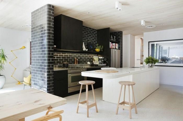ziegelwand in schwarz in der küche kontrastiert schön zur weißen kücheninsel