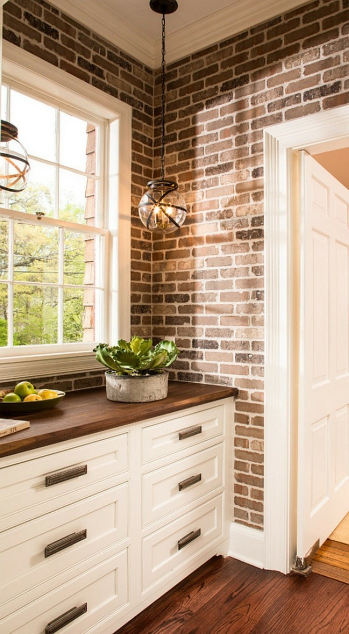 ziegelwand sieht wunderschön mit weißen küchenschränken aus