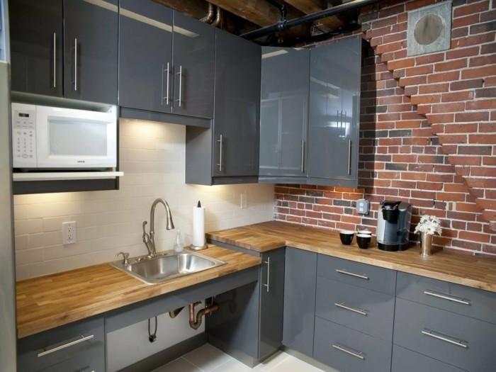 ziegelwand und hölzerne arbeitsoberfläche graue küchenschränke