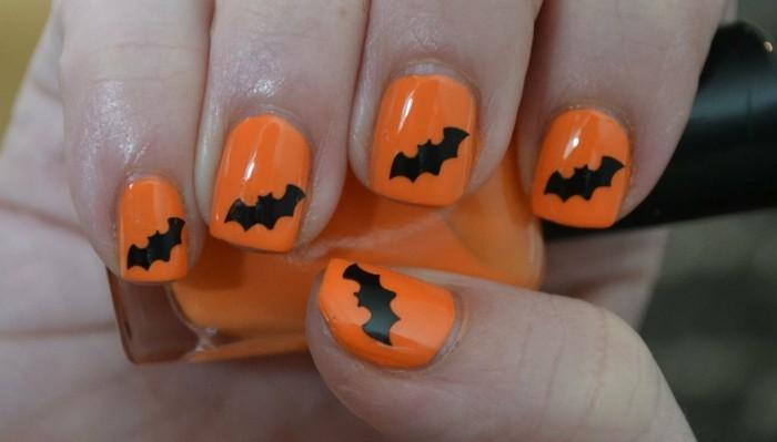 halloween nägel oranger nagellack mit fledermäusen