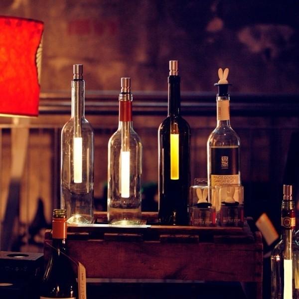 weinflaschen als flaschenlampen auf dem tisch