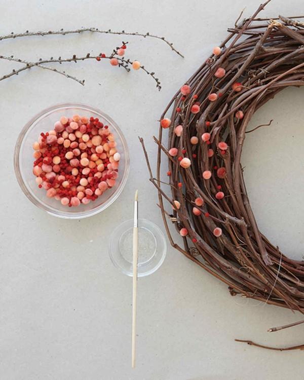 Kranz aus Naturmaterialien geschmückt mit Pompons