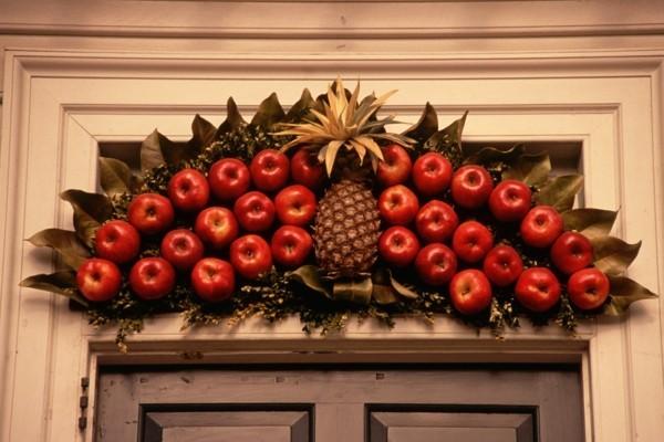 Rustikale weihnachtsdekoration mit Äpfeln für die Eingangstür