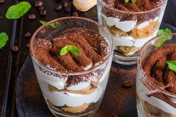 tiramisu im glas mit kakaopulver löffelbiscuits und minzblättern