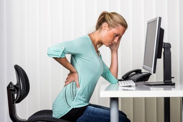 was hilft gegen rückenschmerzen junge Frau im Büro