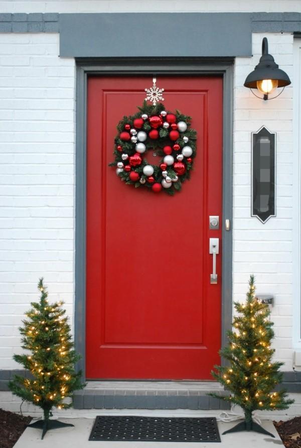 weihnachtsdeko hauseingang rote haustür schöner weihnachtskranz leuchtende tannenbäume