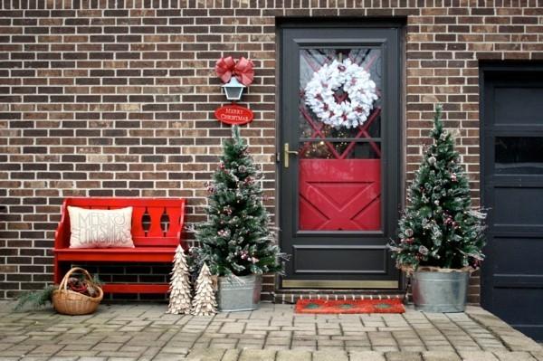 weihnachtsdeko hauseingang weißer weihnachtskranz tannenbäume rote akzente