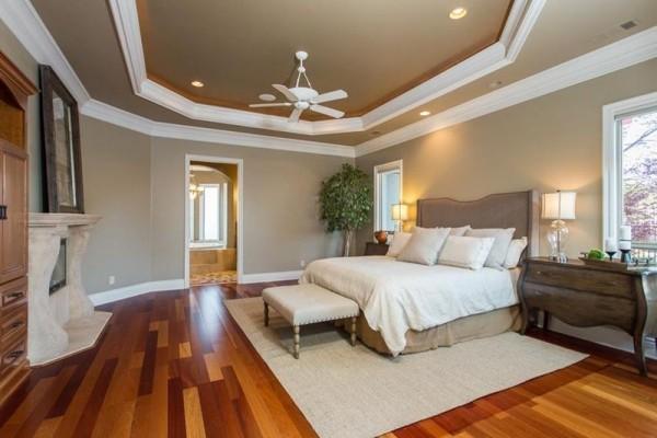Schlafzimmer Ideen geometrisch gestaltete Zimmerdecke Holzboden Kamin