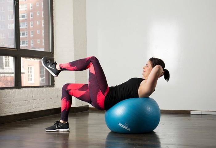 gymnastikball pilates yoga im büro junge frau sportkleidung