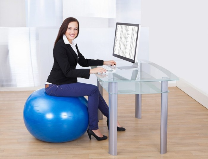 gymnastikball sitzen im büro gesund frau sitzball