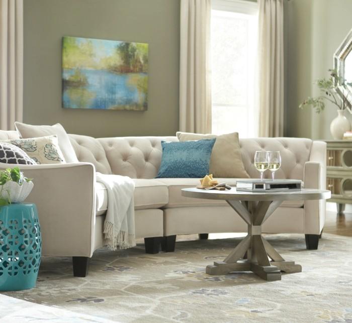 rundes sofa weißes sofa dekokissen blauer beistelltisch schöner teppich