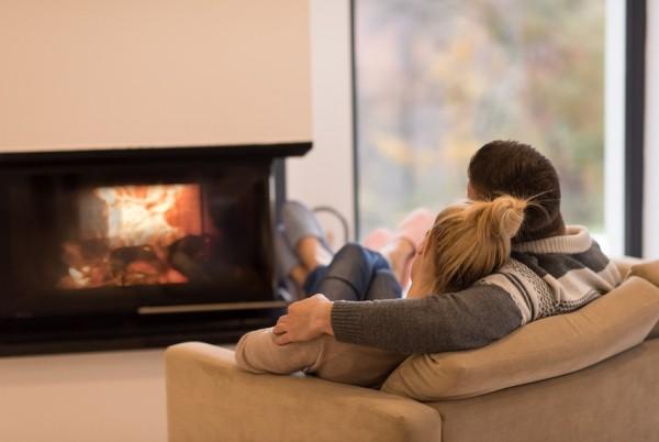 Kuscheln zu zweit Couch vor Kaminfeuer gegen Winterdepression wirken