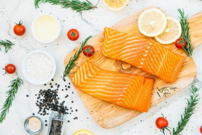Filet Lachs ungekocht mit Zitronen auf Schneidebrett Holt