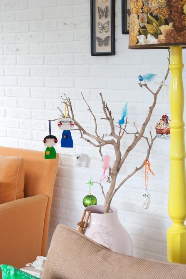 weiße Ziegelwand große Vase Zweige nett dekoriert