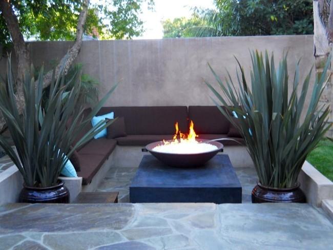 Richtig planen Feuerstelle viele Sitzplätze rund herum hohe grüne Pflanzen
