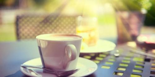 Entspannt eine Tasse aromatischen Kaffee morgens draußen trinken