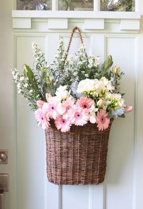 Weidenkorb voller schöner Blumen an der Tür