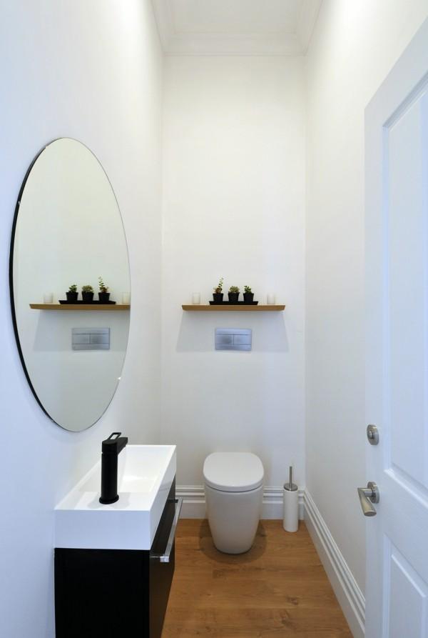 runder badspiegel schlichtes baddesign weiße wände bodenbelag holzoptik