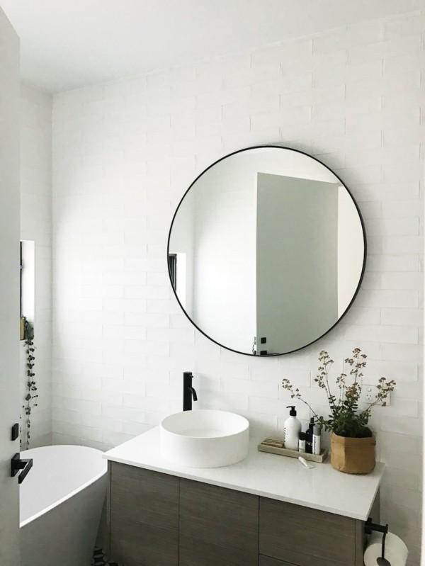 runder badspiegel schwarzer rahmen weiße badezimmerfliesen