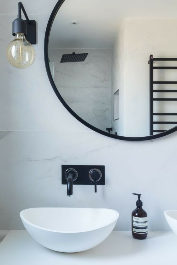 runder badspiegel weiße badezimmerwände schwarze akzente