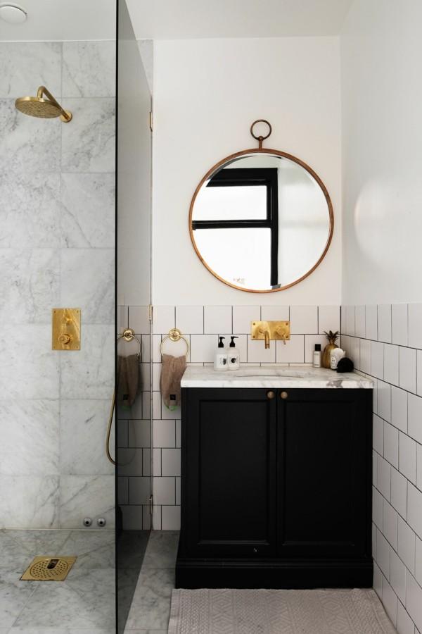 runder badspiegelb schwarzer waschbeckenunterschrank weiße badezimmerfliesen