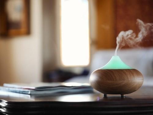 Aromaöldiffuser auf Holztisch im Wohnzimmer