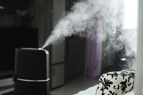 Dampf von Luftbefeuchter zu Hause am Abend in der Dunkelheit