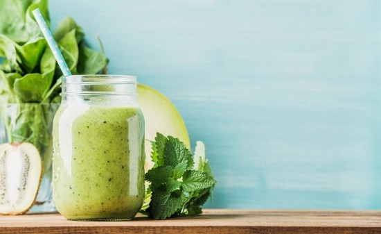 Frisch zubereiteter grüner Smoothie in Glas mit Strohhalm
