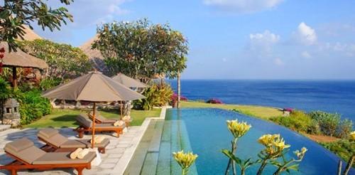 Infinity Pool Gartenblumen Sonnenliegen Schirme viel Grün blaues Meer in der Ferne