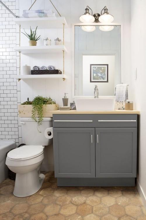 Kleines Badezimmer in Weiß Waschtischschrank grau Spiegel Wandlampen Wanne Metro Fliesen Bodenfliesen in Wabenmuster