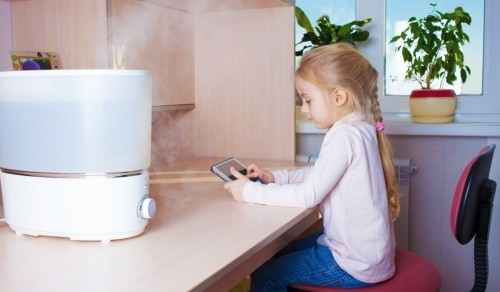 Little girl with tablet pc sitting at the table near humidifier