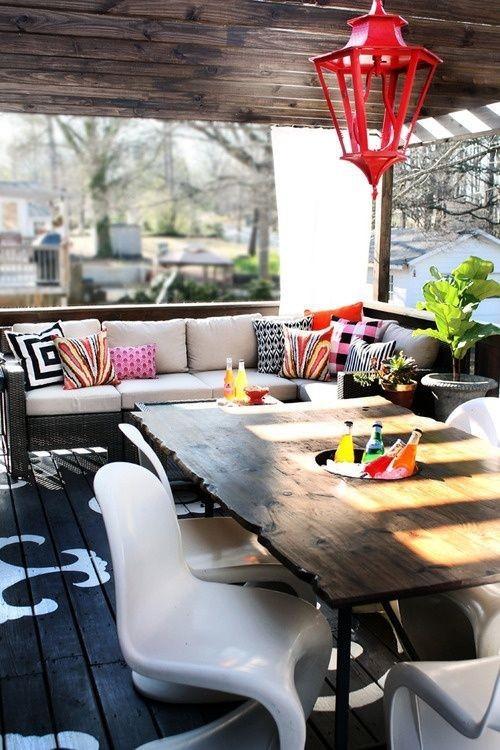 Sommerparty auf der überdachten Veranda Holztisch Acrylstühle Sitzbank Kissen