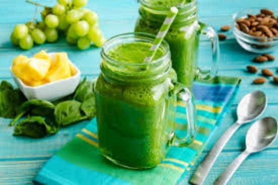 Weckglasbecher gefüllt mit grünem Spinat-Kohl Getränk Trauben grüne Smoothies blaue gestreifte Serviette