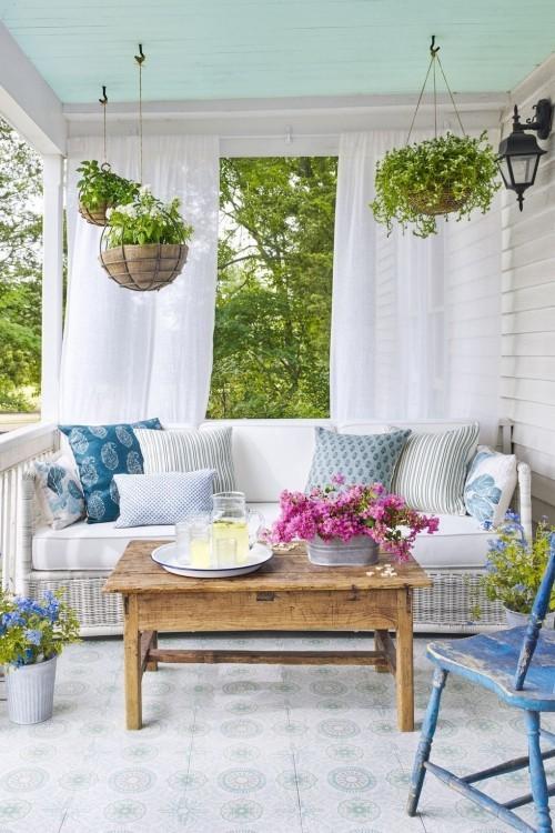Überdachte Veranda in blau-weiß wie kleinen Garten gestalten Blumenampeln hängen lassen