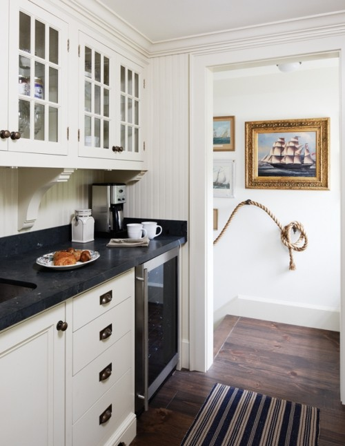 Küche weiße Schränke schwarze Arbeitsplatte Holzboden