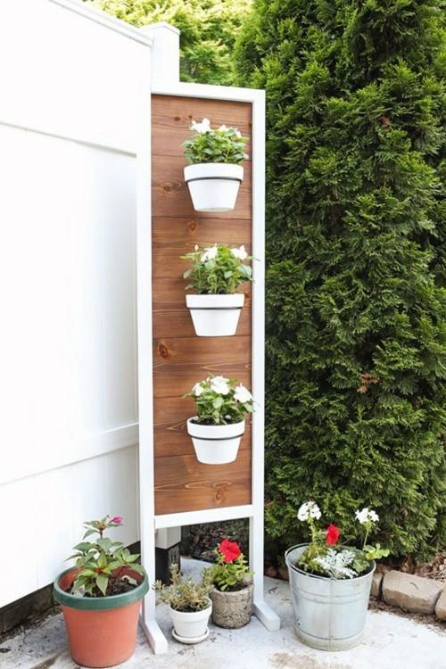 Kleinen Garten gestalten Ständer mit vertikal angeordneten Blumentöpfen in weiß