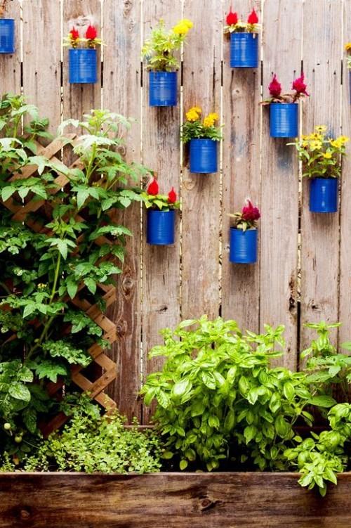 Kleinen Garten größer erscheinen lassen Holzzaun alte Dosen in Blau gestrichen mit Blumen vertikal anordnen viel Grün