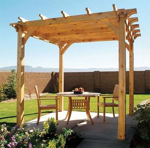 Pergola aus Holz kleiner runder Tisch zwei Stühle Blumen Rasen ruhiger Ort im Garten