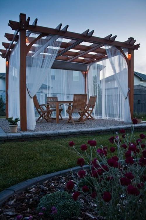 Pergola im Garten weiße Gardinen Sichtschutz abends