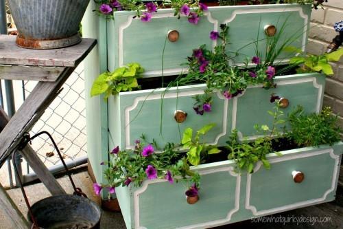 alte Kommode als Blumenständer im kleinen Garten