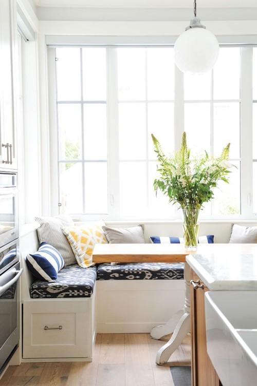 frische Brise in die Sitzecke bringen bunte Kissen grüne Zweige in Vase