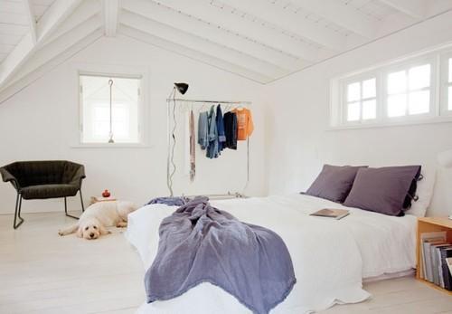 weiß gestaltetes Schlafzimmer azurblaue Akzente Dachschräge Kleiderstange