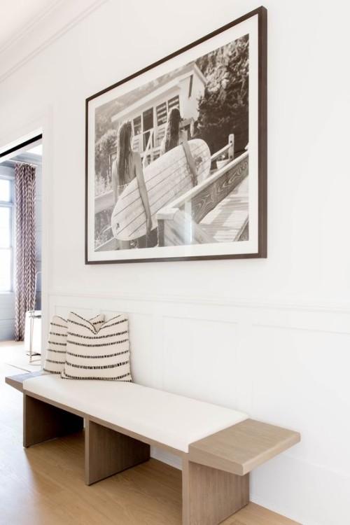 Flur gestalten möglichst simpel aber einladend weiße Wände einfache Sitzbank Deko Kissen Wandbild
